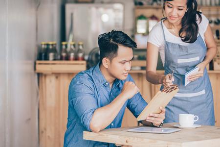 Photo pour portrait of female waitress explain about the menu to her cutomer - image libre de droit