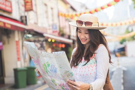 Foto de traveler girl searching right direction on map while exploring asian city - Imagen libre de derechos