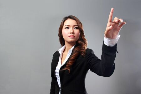 Photo pour Businesswoman pressing button or something. on gray background with copy space for your design. - image libre de droit