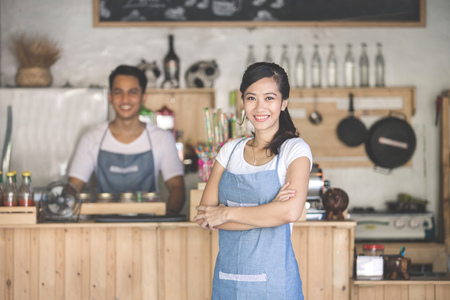 Photo for Successful small business owner standing with crossed arms with partner at the background - Royalty Free Image