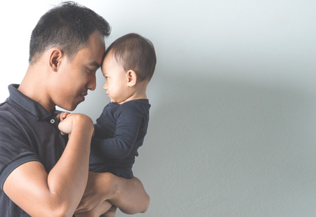Photo for A portrait of a Young Asian father holding his adorable baby on white background - Royalty Free Image