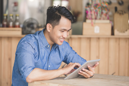 Photo for Image of happy young man using digital tablet in cafe - Royalty Free Image