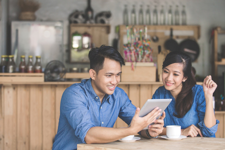 Photo for portrait of two young business partner using tablet together in the cafe - Royalty Free Image