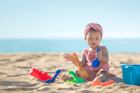 Photo pour Cute baby girl playing with beach toys on tropical beach - image libre de droit
