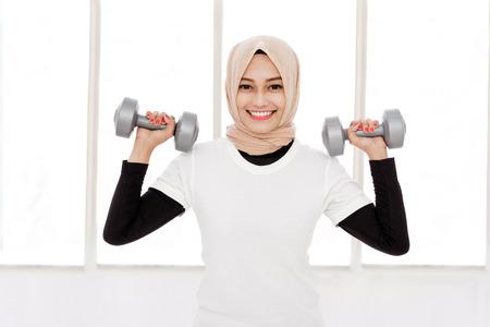 Photo pour portrait of beautiful asian sporty woman lifting dumbbells - image libre de droit