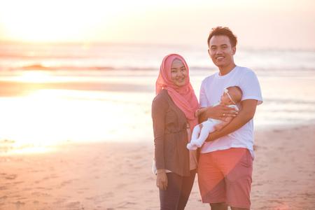 Photo pour portrait of happy parent with newborn baby at the beach having fun together - image libre de droit