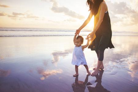 Foto de portrait of a mother is teaching her daughter walks on the beach - Imagen libre de derechos