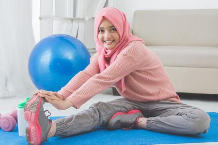 Photo for portrait of healthy asian woman with hijab doing exercise at home - Royalty Free Image