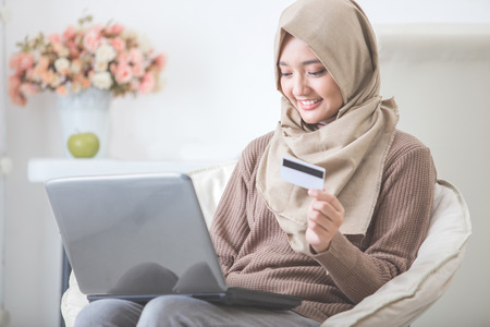 portrait of happy woman purchasing product via online shopping. pay using credit card