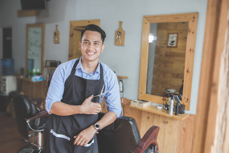 Photo pour Happy young business owner looking at camera while leaning on chair at his barbershop - image libre de droit