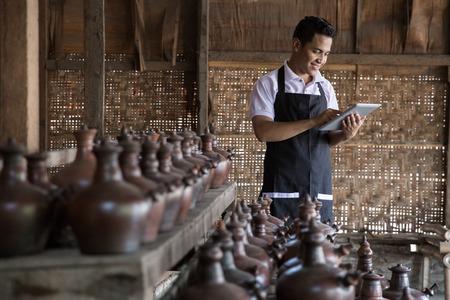 Photo pour Portrait of male potter using digital tablet in pottery workshop. selling his product online - image libre de droit