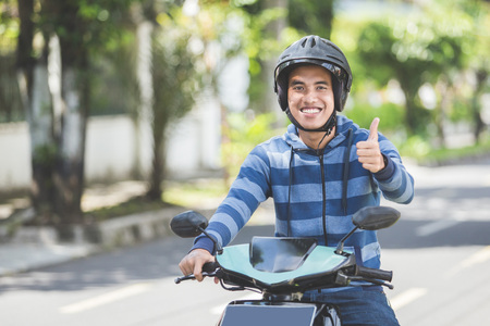 Photo for portrait of happy asian man riding on motorbike in city street and showing thumb up - Royalty Free Image