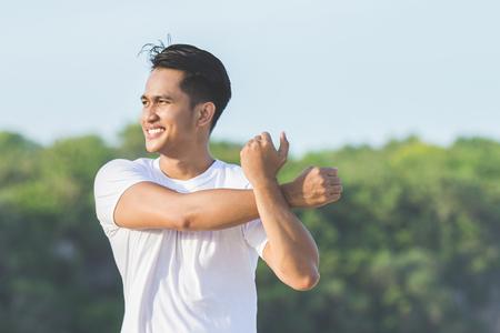 Foto de handsome asian young male warming up before jogging at the beach - Imagen libre de derechos