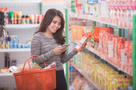 Foto de happy young asian woman shopping at supermarket with check list on her mobile phone - Imagen libre de derechos