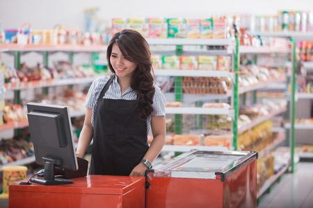 Foto de Portrait of smiling asian female staff standing at cash counter in supermarket - Imagen libre de derechos