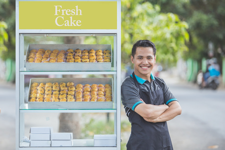 Photo pour small business owner standing proudly in front of his food stall. street food concept - image libre de droit