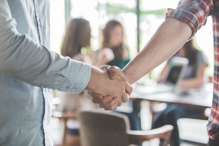 Photo for close up of two young male business partner shake hand in a cafe - Royalty Free Image