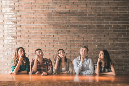 Photo pour portrait of a group of casual people thinking while looking above with copy space - image libre de droit