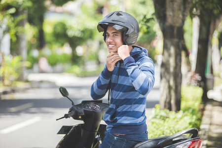 Photo for happy man fastening his motorbike helmet in the city street - Royalty Free Image