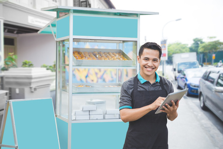 Photo pour happy male entrepreneur with his newly open small business food stall. promoting online using tablet pc - image libre de droit