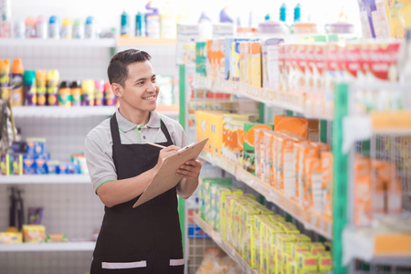 Photo pour Portrait of asian male staff checking the product in supermarket - image libre de droit