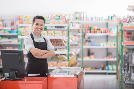 Photo pour Portrait of a smiling shopkeeper in a grocery store - image libre de droit