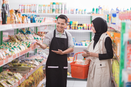 Photo pour portrait of male shopkeeper is helping muslim female customer in supermarket - image libre de droit