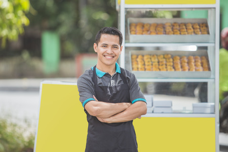 Photo pour small business owner standing proudly in front of his food stall - image libre de droit