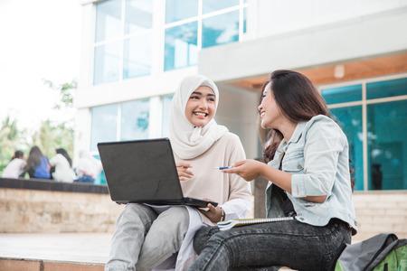 Foto de portrait of two attractive asian college student using laptop on campus - Imagen libre de derechos