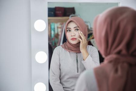 Foto de unhappy muslim woman with hijab looking at her face in the mirror - Imagen libre de derechos