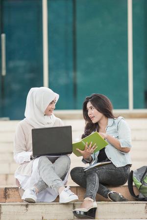 Photo pour portrait of two attractive asian college student using laptop on campus - image libre de droit