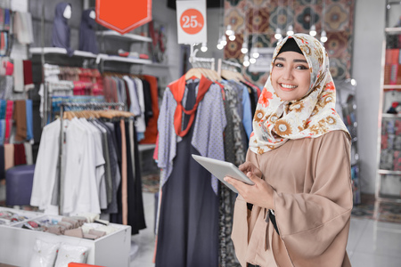 Photo pour Portrait of a young muslim businesswoman with beautiful smile holding digital tablet while standing in her fashion boutique, female owner - image libre de droit