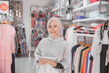 Photo for Portrait of a young muslim businesswoman with beautiful smile holding digital tablet while standing in her fashion boutique, female owner - Royalty Free Image