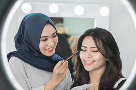 Photo pour beautiful Make-up artist applying cosmetic with a brush on woman eyelids - image libre de droit