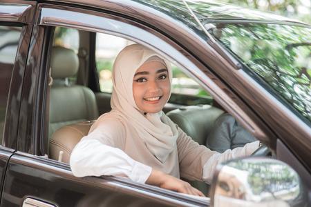 Photo pour portrait of muslim asian young woman driving her car - image libre de droit