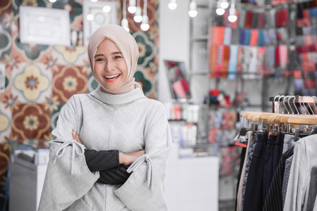 Foto de portrait of attractive asian female business owner standing crossed arm in her boutique fashion store. muslim entrepreneur concept - Imagen libre de derechos