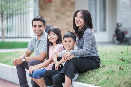 Photo pour happy asian family in front of their house - image libre de droit