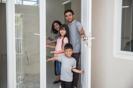 Photo pour happy family with kids open their house door - image libre de droit