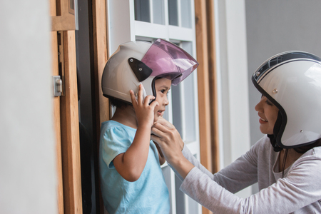 Photo for young happy little girl wearing helmet with her mother - Royalty Free Image