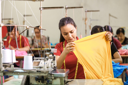 Photo pour Seamstress in textile factory sewing using industrial sewing machine - image libre de droit