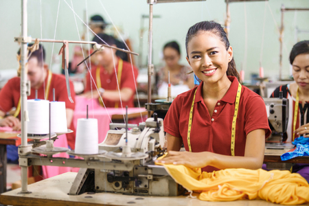 Photo pour Seamstress in textile factory smiling while  sewing - image libre de droit