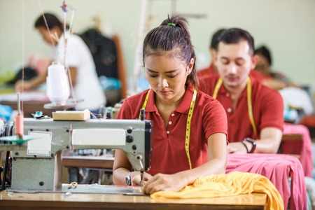 Photo pour Seamstress in textile factory sewing with industrial sewing mach - image libre de droit