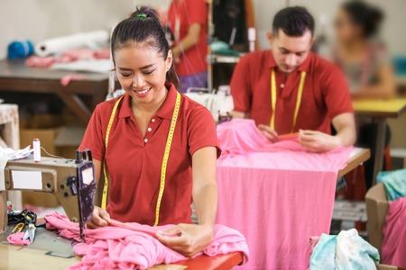 Photo pour seamstress measuring a fabric at garment - image libre de droit