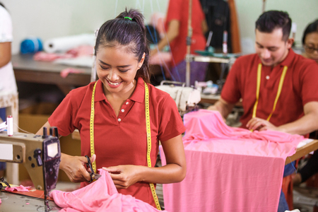 Photo pour seamstress cutting a fabric at clothing factory - image libre de droit