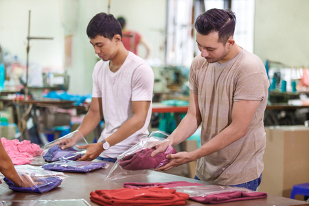Photo pour employees in textile factory packaging their products - image libre de droit