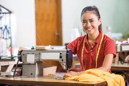 Photo pour Seamstress in textile factory smiling while  sewing with industr - image libre de droit