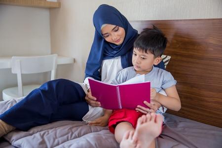 Photo pour mother reading a book with her boy - image libre de droit