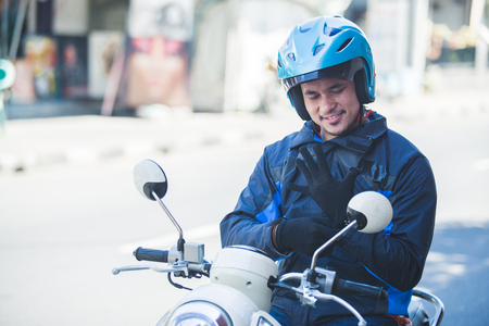 Photo for motorcycle taxi driver wearing his gloves for safety riding - Royalty Free Image