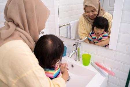 Foto de mom help her kid to wash her hands - Imagen libre de derechos