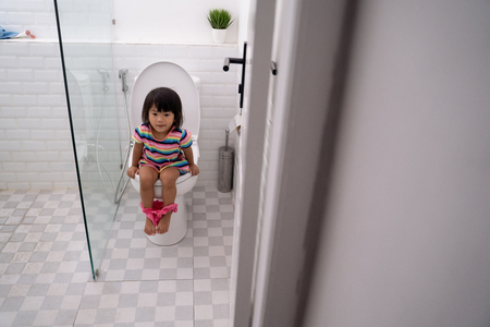Foto de child sitting and learning how to use the toilet - Imagen libre de derechos